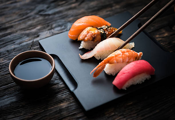 close up of sashimi sushi set with chopsticks and soy - japanese food stock photos and pictures