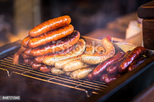 Close up image of sausages, bratwurst and wieners being flame-grilled at a Market. Horizontal colour image with copy space.