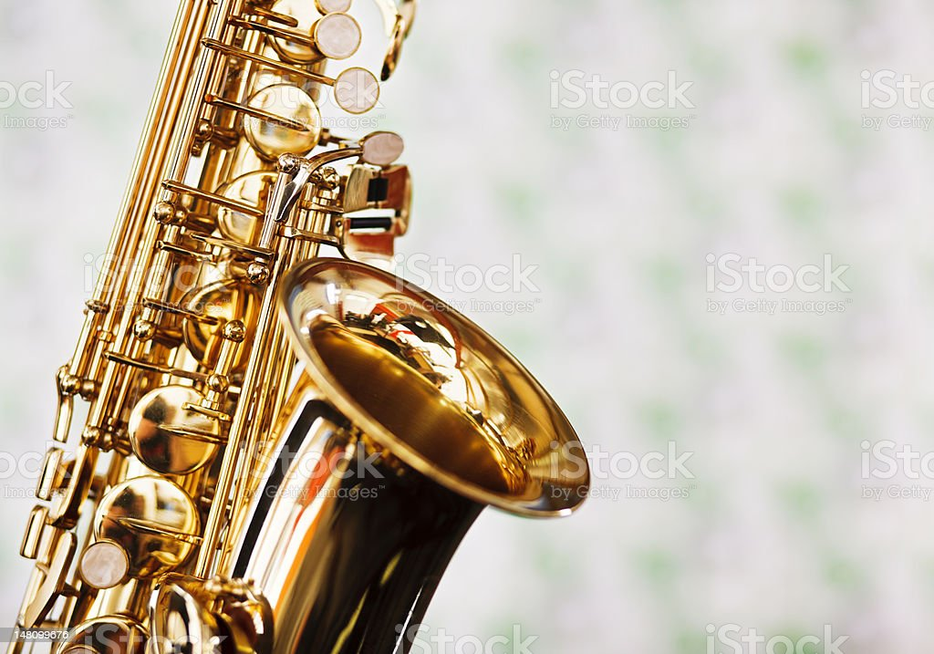 Close up of saxophone against faded green and white fabric royalty-free stock photo