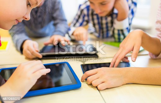 istock close up of school kids playing with tablet pc 487093020