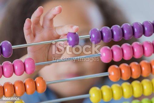 istock Close up of schoolgirl using abacus 666835504