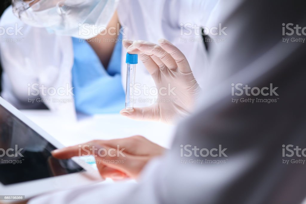 Close up of scientific research team with clear solution in laboratory zbiór zdjęć royalty-free