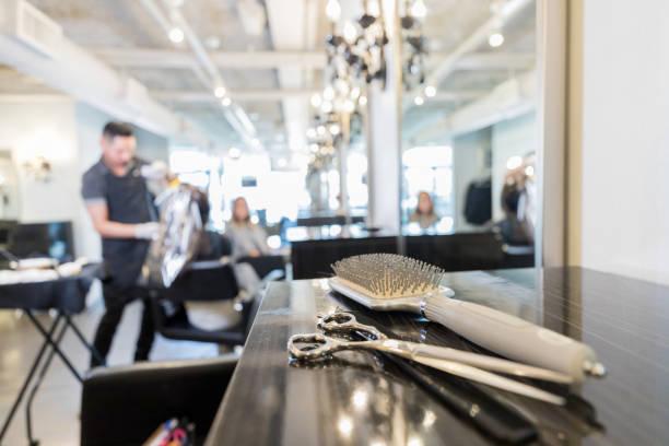 gros plan de ciseaux et brosse à cheveux dans un salon de coiffure - salon de coiffure photos et images de collection
