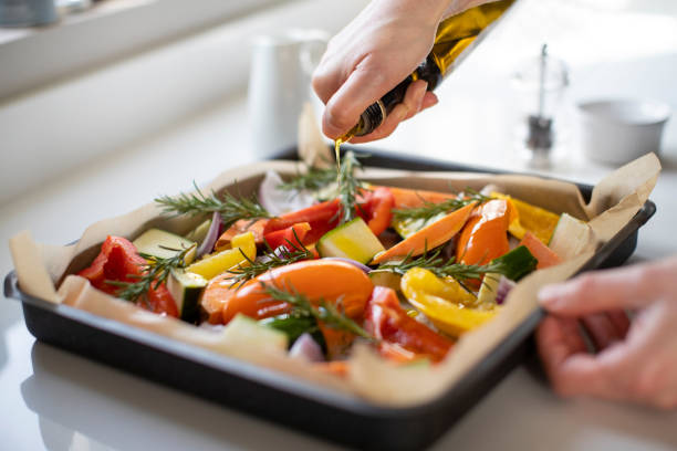 close up of seasoning tray of vegetables for roasting with olive oil ready for vegan meal - prażony zdjęcia i obrazy z banku zdjęć