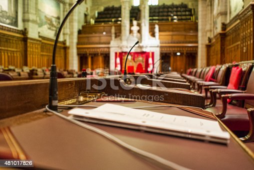 Close up of a Senator's desk with paperwork.  Image taken in the chambers of the Senate of Canada, in the Parliament Buildings in Ottawa, Canada.  The Speaker's chair can be seen in the background.  A narrow depth off field has been applied to this image.