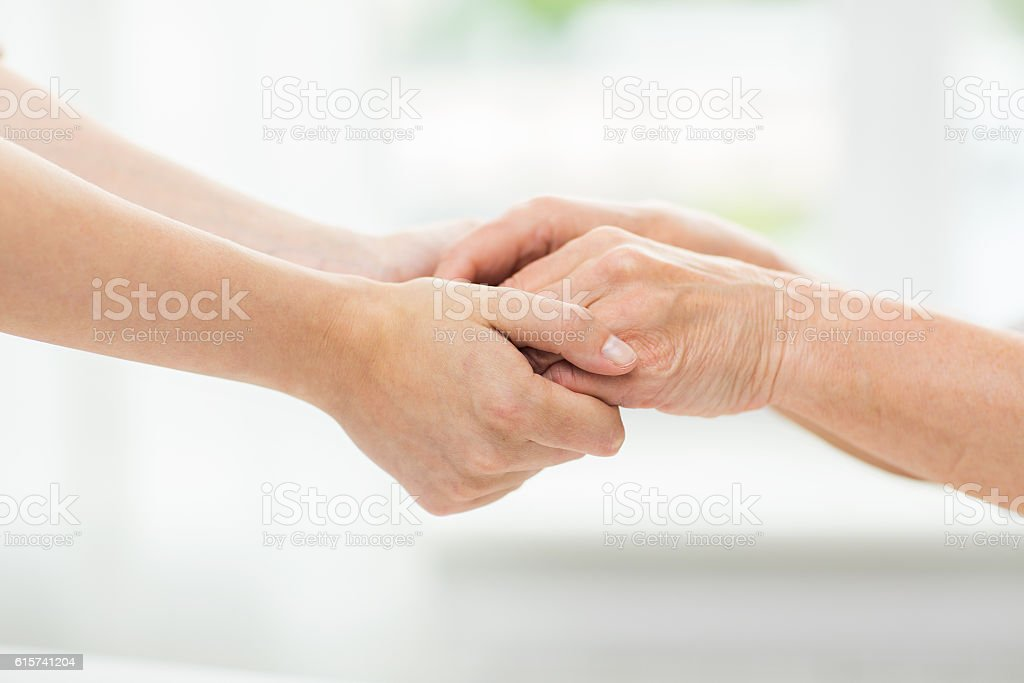 close up of senior and young woman holding hands stock photo