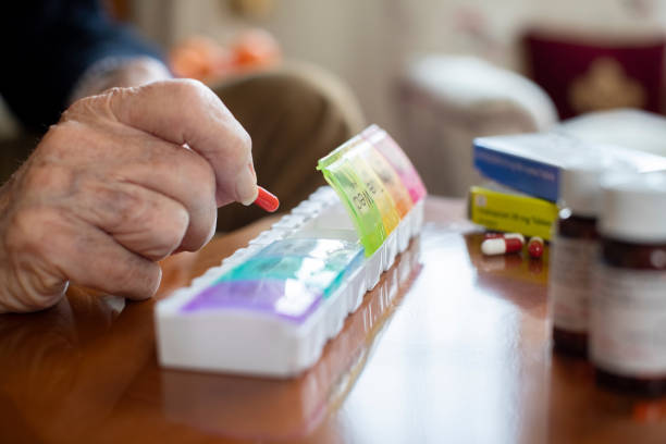 Close Up Of Senior Man Organizing Medication Into Pill Dispenser Close Up Of Senior Man Organizing Medication Into Pill Dispenser pill container stock pictures, royalty-free photos & images