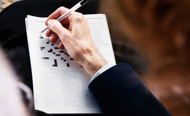 Close up of senior man's hand with pen on crossword puzzle stock photo