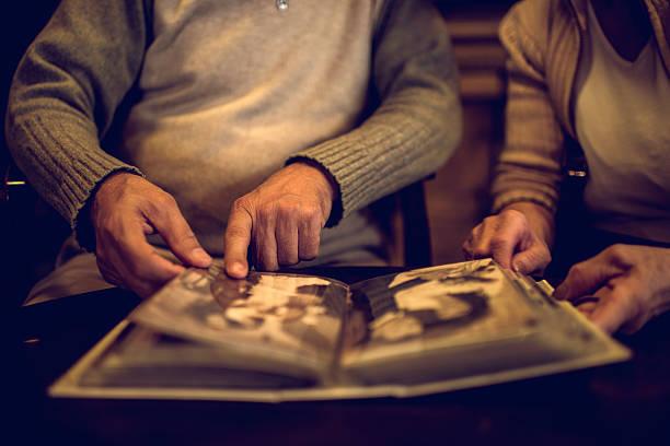 close up of senior people remembering their old photos. - senior fotoboek stockfoto's en -beelden