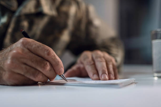 Close up of senior soldier taking notes. Close up of mature army soldier writing a letter. sergeant stock pictures, royalty-free photos & images