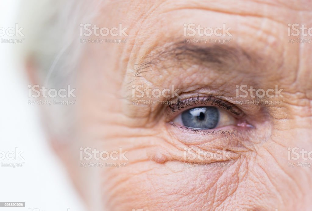 close up of senior woman face and eye stock photo