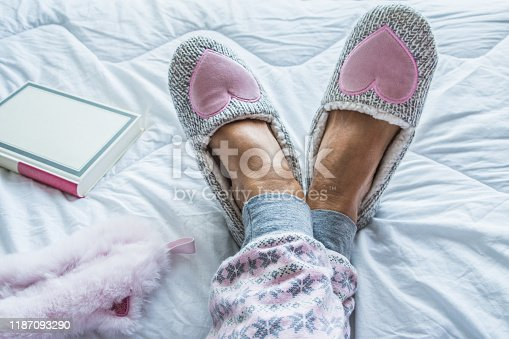 Close Up of Senior Woman Legs in Fluffy Slippers on the Bed