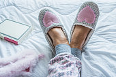 istock Close Up of Senior Woman Legs in Fluffy Slippers on the Bed 1187093290