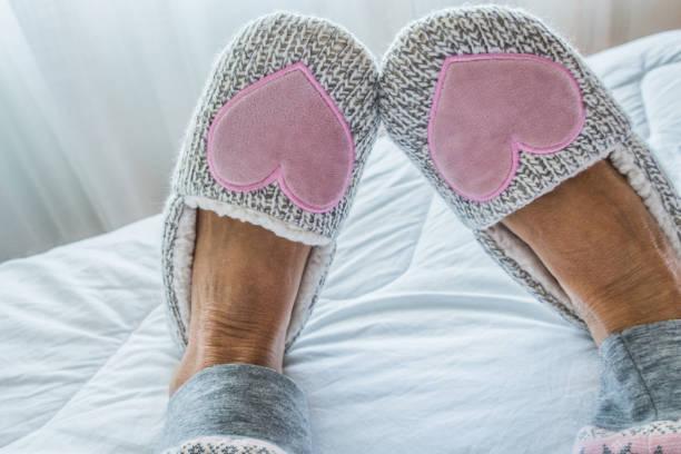 Nahaufnahme von Senior Woman Legs in flauschigen Hausschuhen auf dem Bett – Foto