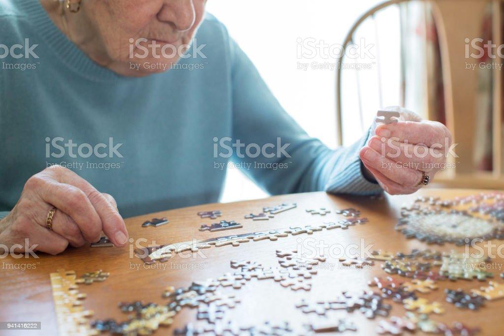 Close Up Of Senior Woman entspannend mit Puzzle zu Hause – Foto