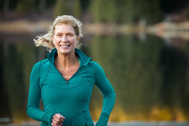 Close up of senior woman running by lake.
