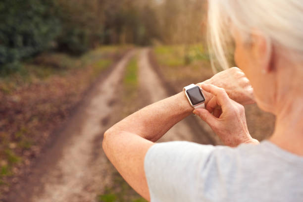 Close Up Of Senior Woman Running In Countryside Exercising Checking Smart Watch Fitness Activity App stock photo