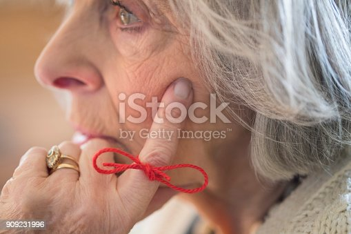 istock Close Up Of Senior Woman With String Tied Around Finger As Reminder 909231996