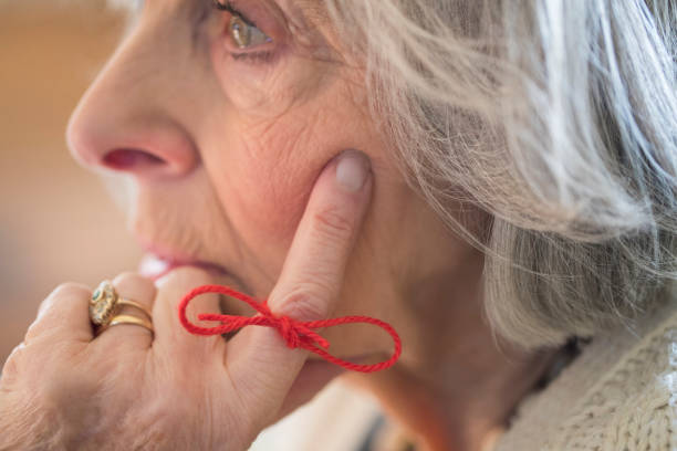 Close Up Of Senior Woman With String Tied Around Finger As Reminder stock photo