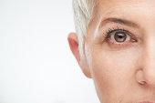 Close up of senior woman`s eye. Gray short hear.