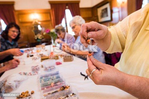 Close up of Senior woman's hands holding handmade beaded earrings