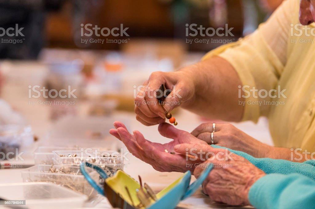 Close up of senior women's hands holding beads stock photo