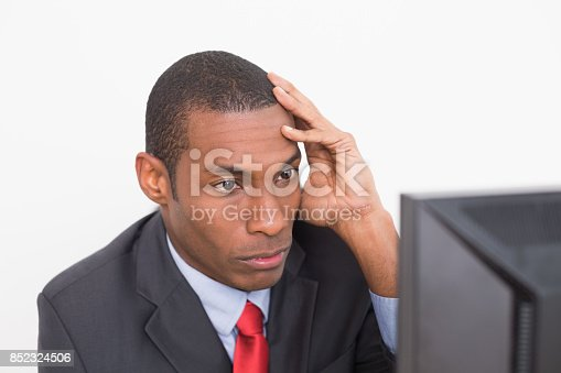 Close up of a serious young Afro businessman looking at computer against white background