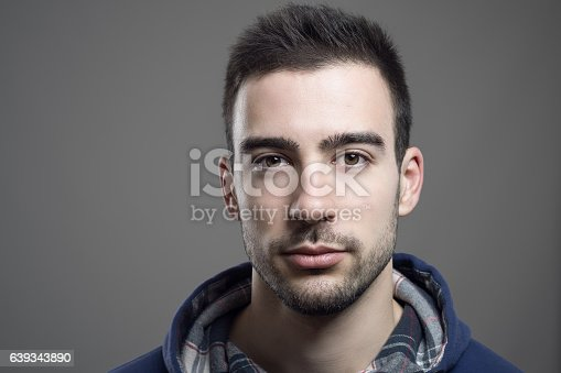 Close up of serious young unshaven man wearing hoodie looking at camera