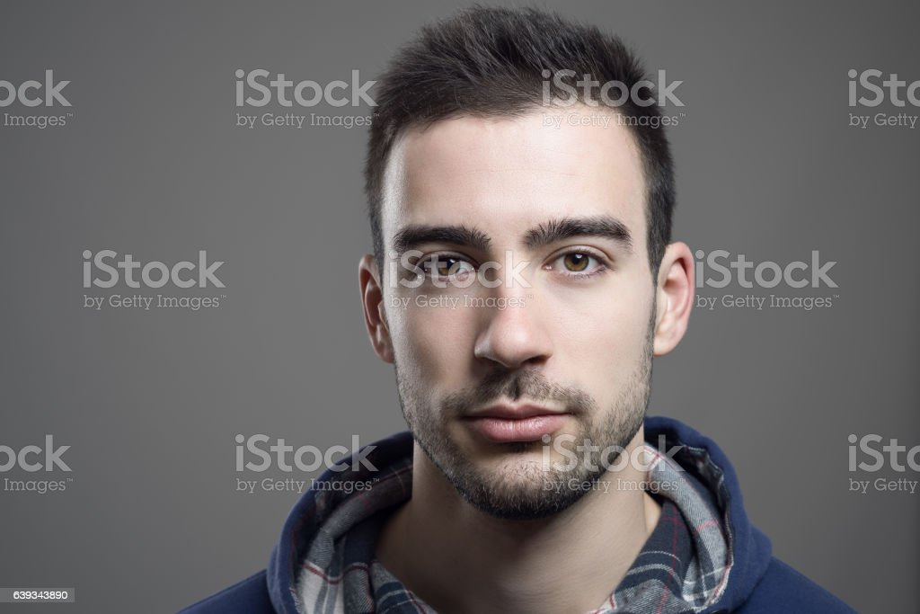 Close up of serious young unshaven man wearing hoodie stock photo