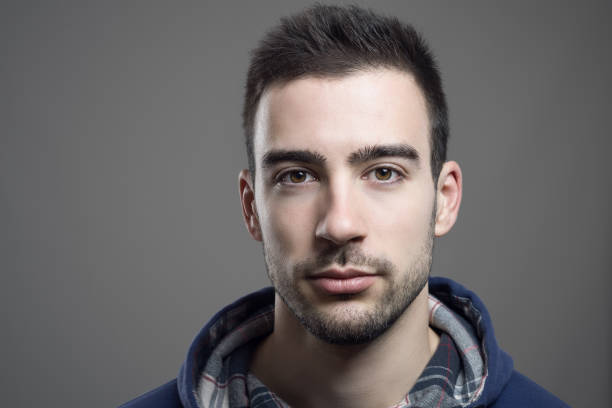 Close up of serious young unshaven man wearing hoodie - foto de stock