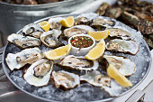 Close Up of Server with Tray of Fresh Shucked Oysters with Lemon Wedges Served as Appetizer. tray with open oysters