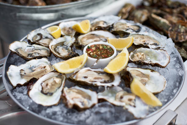 close up of server with tray of fresh shucked oysters with lemon wedges served as appetizer - oyster stock pictures, royalty-free photos & images