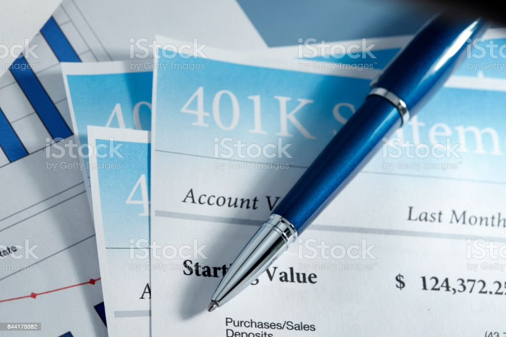 Close Up Of Several 401k Statements With ballpoint pen On Top stock photo