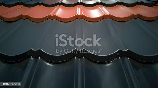 Close up of several rows of plastic roofing of various colors,black,gray,orange brown,in shape of tiles outside on sunny day.Outdoor showcase of building materials store.Horizontal banner,copy space