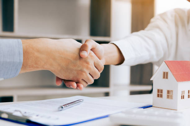 close up of shaking hands with customer and real estate broker after signing a contract in home office. - real estate law stock photos and pictures
