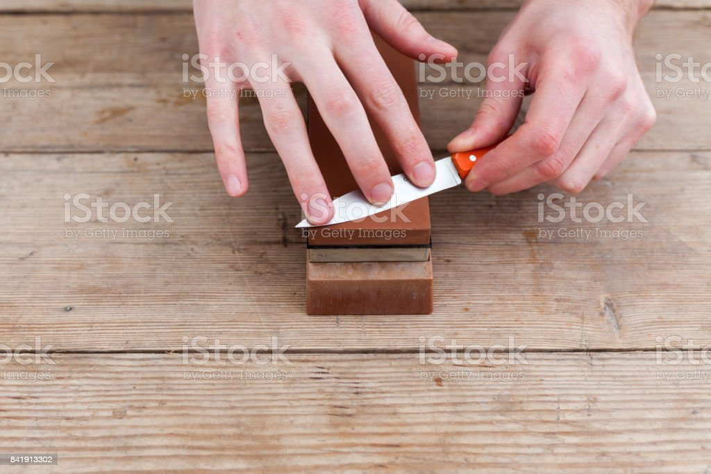 Close up of sharpening the knife with a whetstone on a wooden background. Top view stock photo