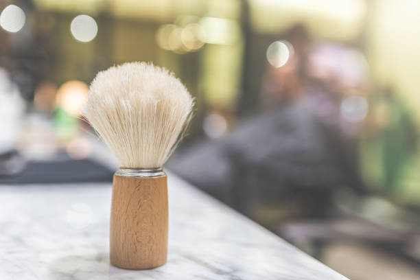 Close up of shaving brush on table at barber shop. Space for copy. Wooden brush for shaving beard. Blurred background of men hair salon. shaving brush shaving cream razor old fashioned stock pictures, royalty-free photos & images