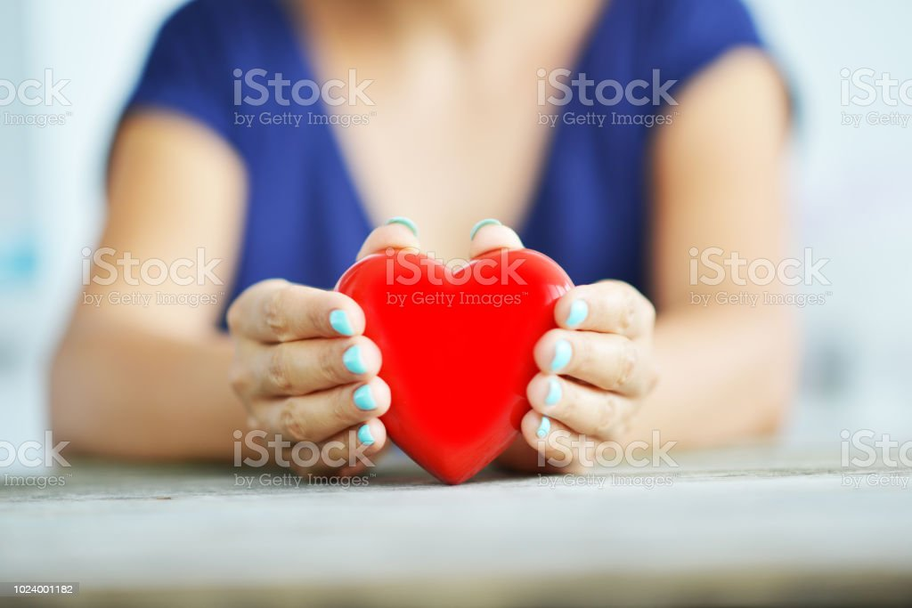 Close up of shiny red heart in young woman's hands, charity concept stock photo