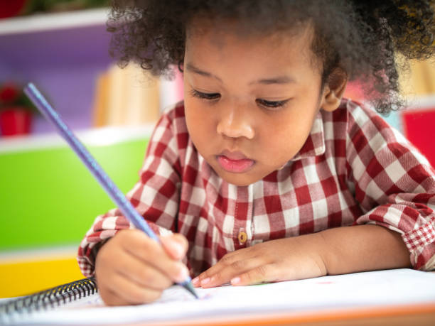 Close up of shot Cute little African American kid concentrate draw full colour of picture with colour pencil with friend in backgrounds. Kindergarten school concept, children education, preschool. Close up of shot Cute little African American kid concentrate draw full colour of picture with colour pencil with friend in backgrounds. Kindergarten school concept, children education, preschool. nerd hairstyles for girls stock pictures, royalty-free photos & images
