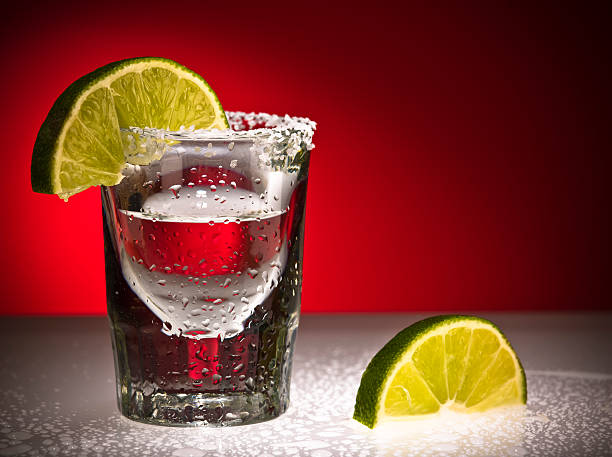 Close up Of Shot Glass and Limes  tequila shot stock pictures, royalty-free photos & images