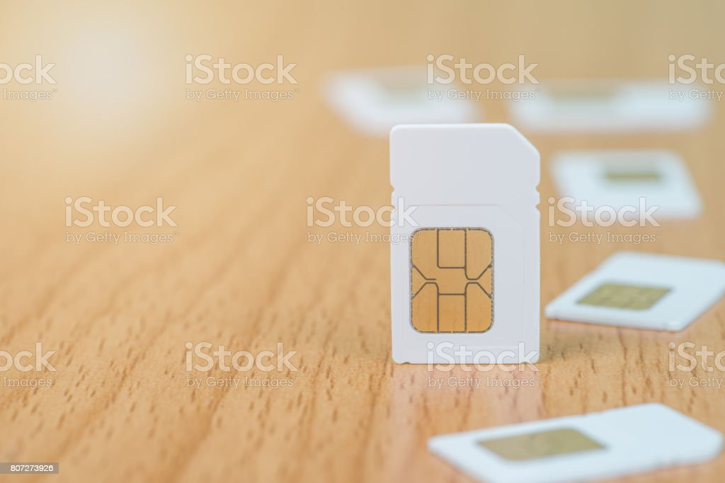Close up of sim card on wooden table with copy space. stock photo