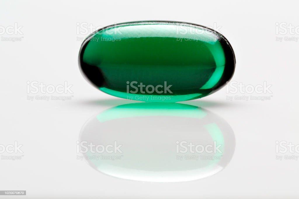 Close up of single green gelatin capsule on white background. Macro shot. stock photo