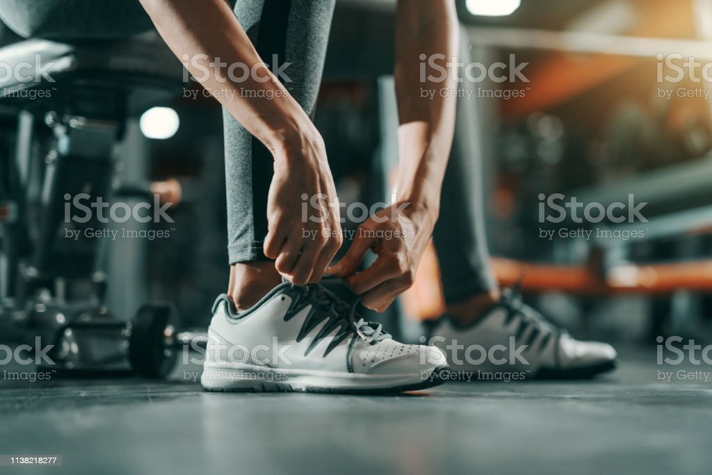 Close Up Of Slim Caucasian Woman Tying Shoelace In Gym At Night Be Stronger Than Your Excuses Stock Photo Download Image Now Istock
