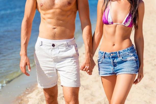 スリム フィット男性カップル、ビーチの上を歩くをクローズ アップ。若い家族の休息 ストックフォト