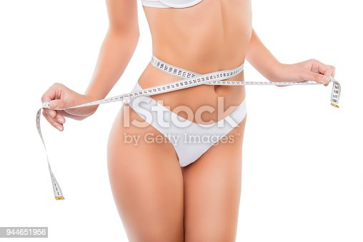 1090563354 istock photo Close up of slim woman measuring her waist's size with tape measure 944651956