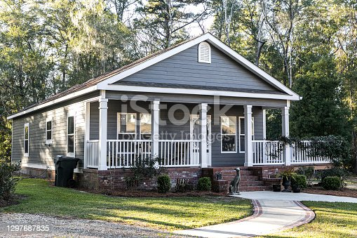 istock Close up of small blue gray mobile home with a front and side porch with white railing 1297687835