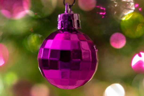 close up of small red disco ball ornament on a christmas tree with bokeh lights in the background stock photo