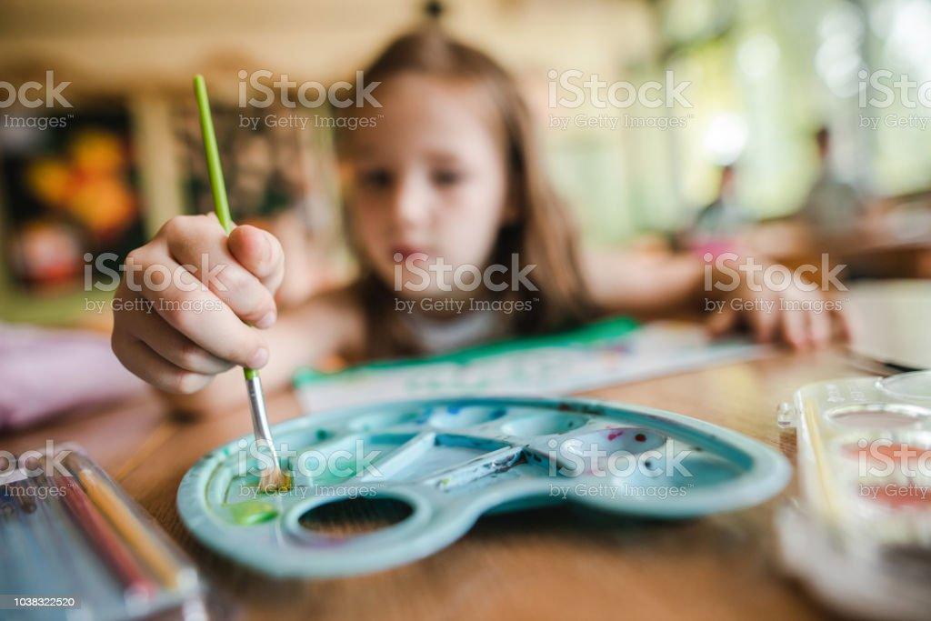 Cerca del pequeño estudiante utilizando pinturas de acuarelas en clase de arte. - foto de stock