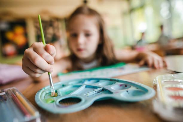 cerca del pequeño estudiante utilizando pinturas de acuarelas en clase de arte. - clase de arte fotografías e imágenes de stock