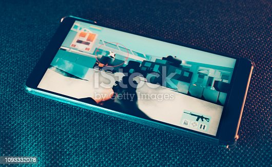 Mobile phone lays on couch. It shows a sequence from an action game. It features a crosshair and a machine gun.